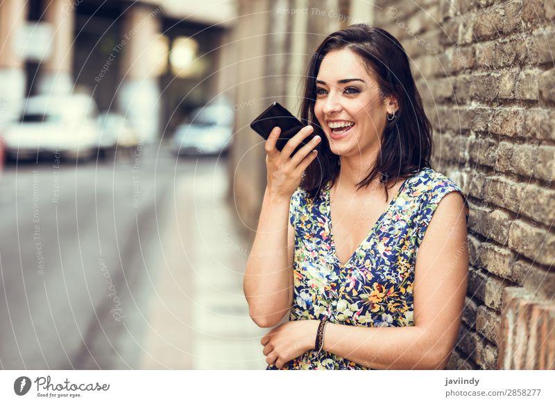 Lächelnde junge Frau nimmt Sprachnotiz in ihrem Smartphone auf. Lifestyle Stil Glück schön Haare & Frisuren Telefon PDA Technik & Technologie Mensch feminin