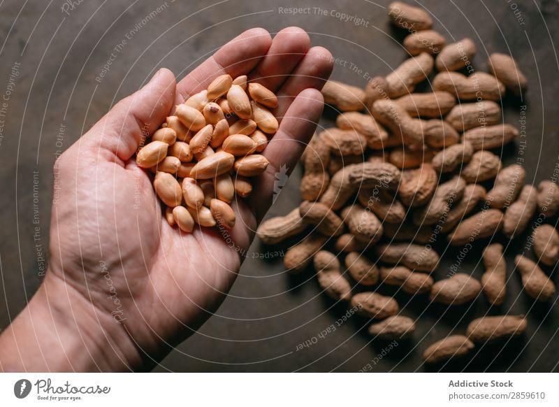 Mann hält Erdnüsse in der Hand. Landwirtschaft Sortiment Hintergrundbild Schneidebrett regenarm Lebensmittel frisch Frucht Gesundheit Halt Zutaten Nuss roh