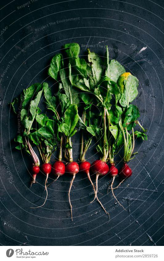 Radieschen auf dunklem Hintergrund Vor dunklem Hintergrund ökologisch Lebensmittel frisch grün Ernte Gesundheit Zutaten Blatt organisch rot Gemüse