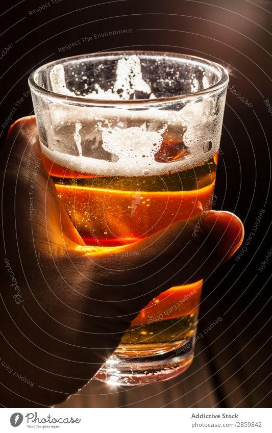 Männerhand hält ein Glas Berr mit Licht im Hintergrund. Alkohol Bier Bar Getränk Flasche Brauerei Coolness Handwerk trinken trockene, kräftige Schaum