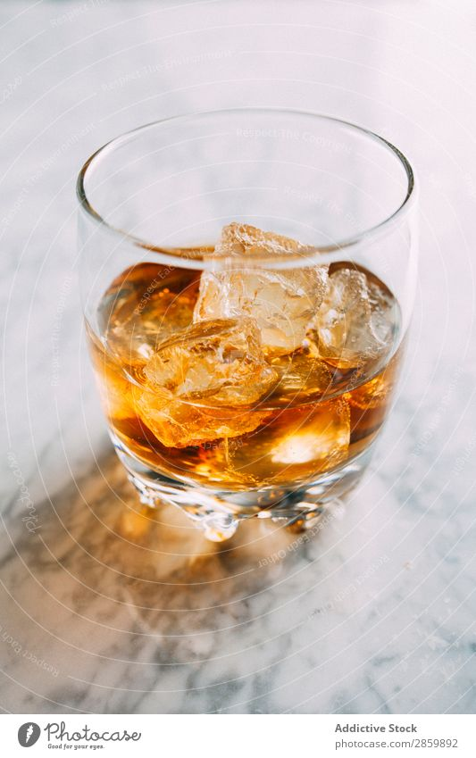 Ein Glas Whiskey auf Eis in Marmortisch Alkohol Amber Hintergrundbild Bar Barmann Barkeeper Getränk Flasche Bourbon Weinbrand Cognac trinken gold on the rocks