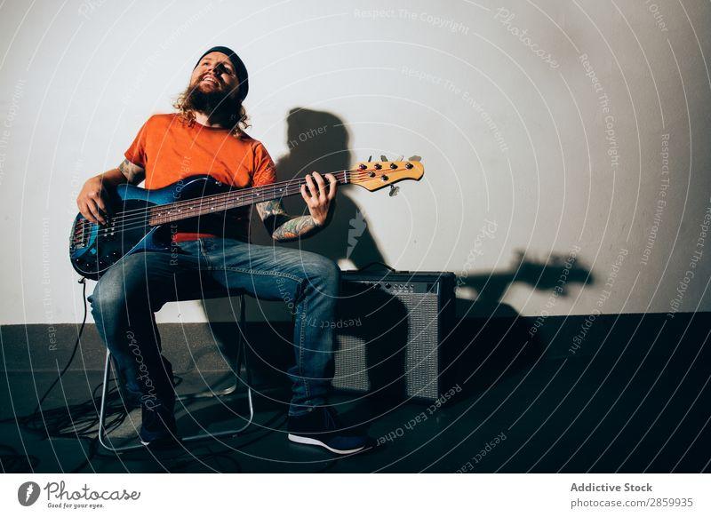 Cooler junger Mann beim Bass spielen akustisch alternativ Verstärker Künstler Band Konzert Elektrogitarre Entertainment Gitarre Gitarrenspieler Schickimicki