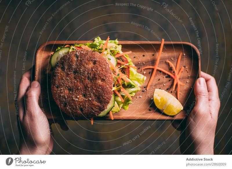Frau hält ein Tablett mit einem vegetarischen Sandwich. Avocado Biografie Brot Brötchen Burger Möhre Gurke lecker deluxe Diät Öko ökologisch Lebensmittel frisch