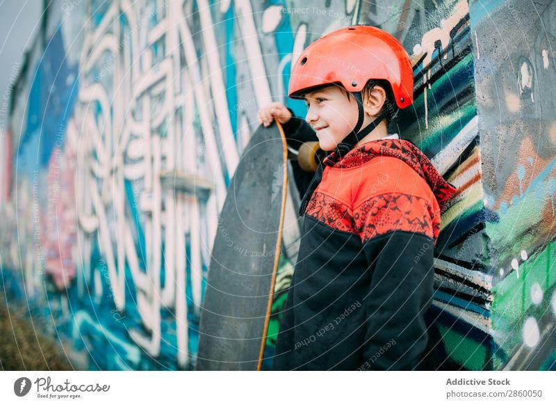 Kind mit langem Brett Holzplatte Junge Kaukasier Gerichtsgebäude Graffiti Helm lernen Longboard Außenaufnahme Park Spielen Schutz Schlittschuhe Skateboard
