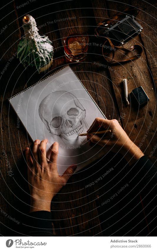 Schädelzeichnung Schuss von oben Kunst Künstler Flasche Fotokamera Kerze Kohlenstoff Zigarre Kreativität dunkel zeichnen Zeichnung Glas Hand