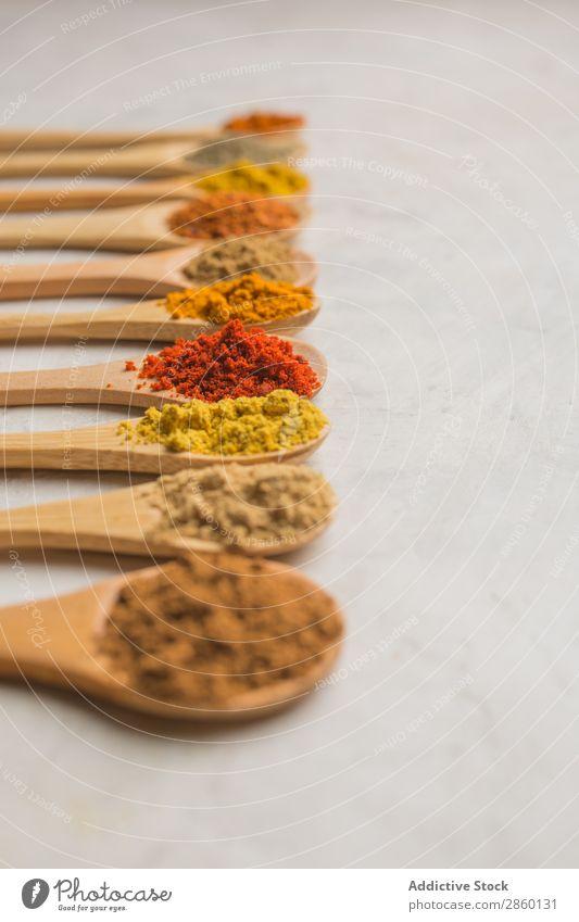 Verschiedene Gewürze in Holzlöffeln aromatisch Hintergrundbild Zimt Gewürznelke Textfreiraum Koriander Kümmel Curry dunkel regenarm flache Verlegung