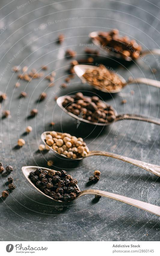 Gewürze auf Löffeln aromatisch Hintergrundbild Gewürznelke Textfreiraum Koriander Kümmel dunkel regenarm flache Verlegung Lebensmittel Vogelperspektive Zutaten
