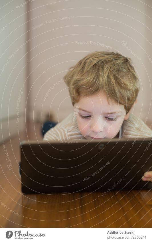 Blonder und süßer Junge spielt mit dem Tablett. blond Kaukasier Kind Computer Tag digital elektronisch im Innenbereich Lifestyle Spielen Bildschirm