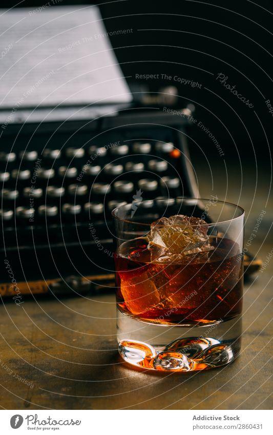 Ein Glas Whiskey und eine Retro-Schreibmaschine. Alkohol Amber analog Antiquität Getränk Bourbon Weinbrand Charakter klassisch Cognac Kreativität trinken gold