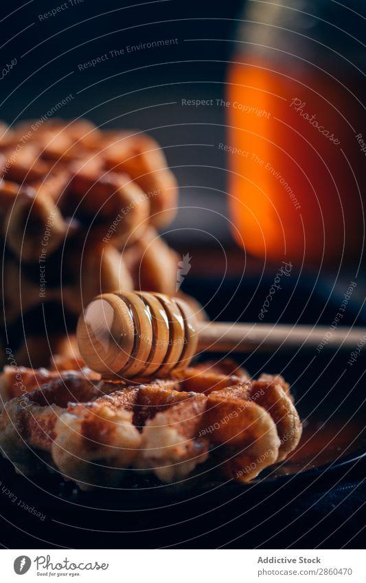 Waffeln in einem Gitter mit Puderzucker und Honig backen Belgier Frühstück Butter Kuchen Nahaufnahme Koch Dessert dick Geschmack Lebensmittel Raster Milch