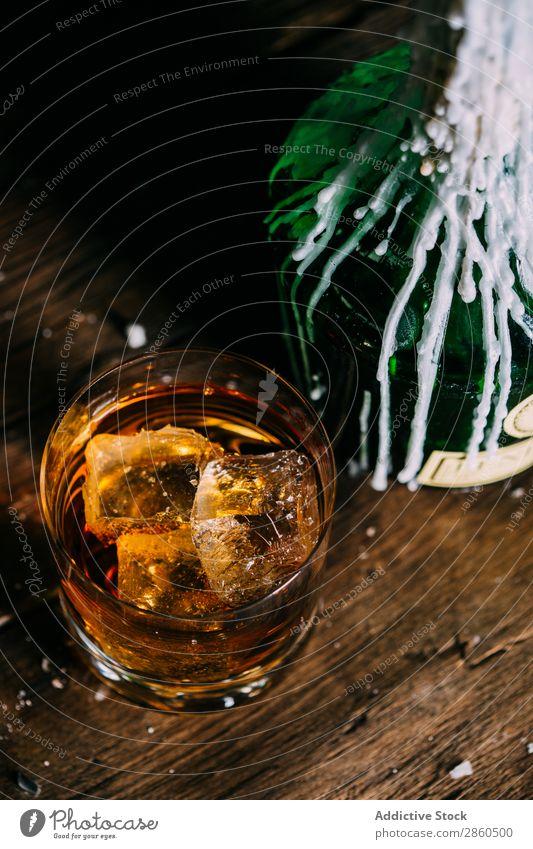Ein Glas Whiskey auf einem Holztisch Alkohol Amber Hintergrundbild Bar Barmann Barkeeper Getränk Flasche Bourbon Weinbrand Cognac trinken gold Hand Eis