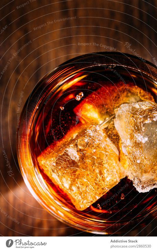 Ein Glas Whiskey auf einem Holztisch Alkohol Amber Hintergrundbild Bar Barmann Barkeeper Getränk Flasche Bourbon Weinbrand Cognac dunkel trinken gold Eis Rum