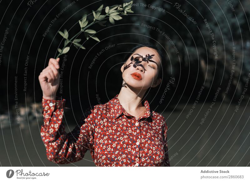 Asiatin mit Astschatten im Gesicht Frau Jugendliche attraktiv Kleid rot asiatisch Japaner Schatten Teich Natur Park Schließfläche Augen geschlossen schön