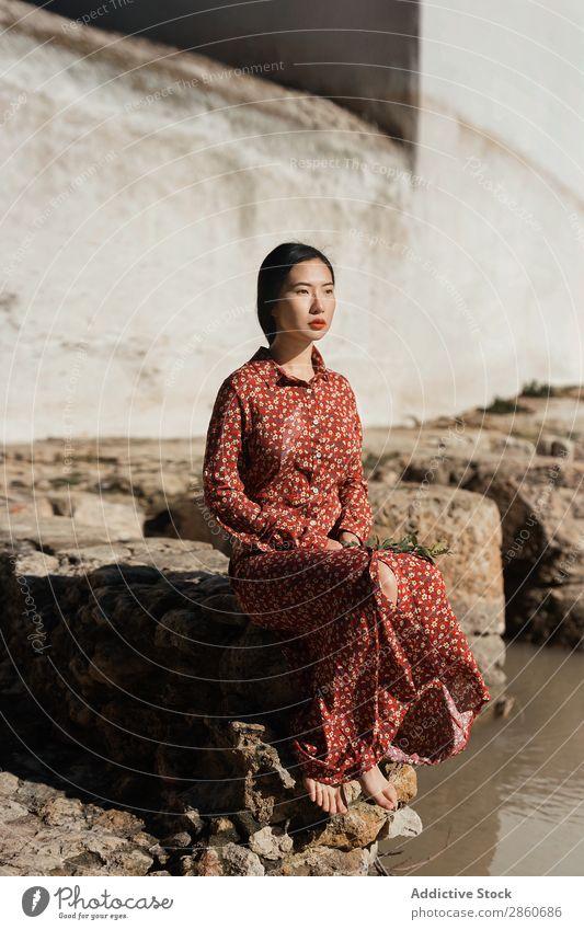 Hübsche asiatische Frau am Teich sitzend Jugendliche attraktiv Kleid rot Japaner Boden