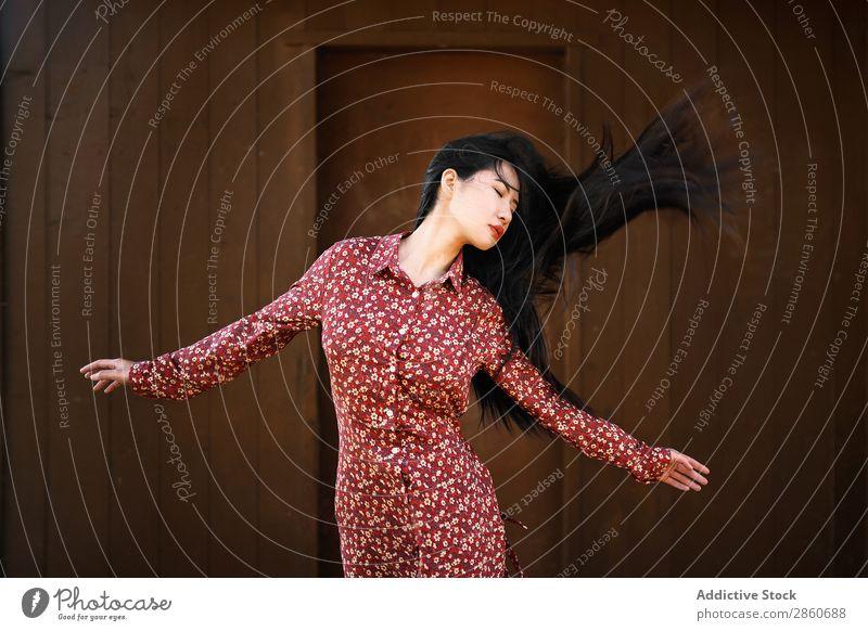 Asiatin schüttelndes Haar Frau Jugendliche attraktiv Kleid rot asiatisch Japaner Behaarung Schütteln Freude Augen geschlossen brünett schön Beautyfotografie
