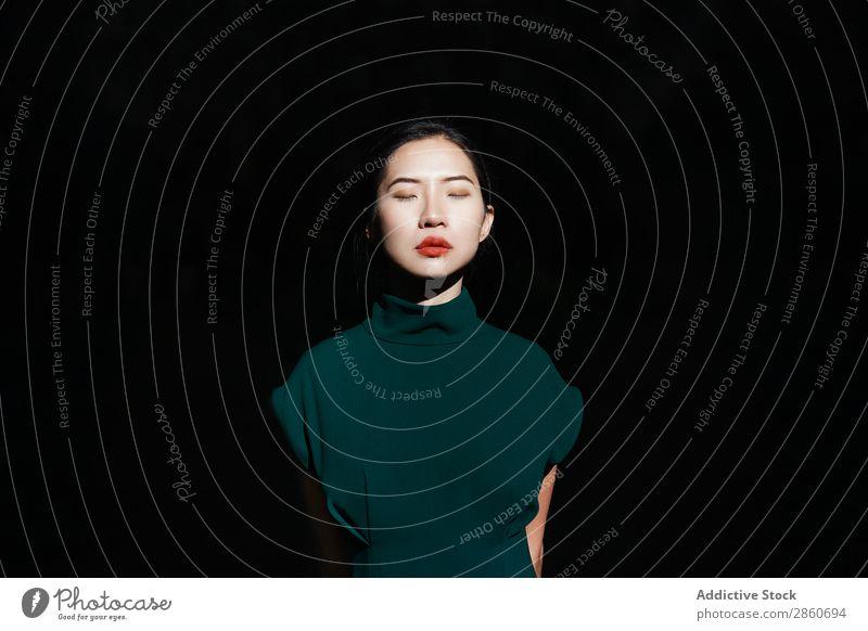Asiatin mit geschlossenen Augen im Wald Frau Jugendliche attraktiv Kleid grün asiatisch Japaner schwarzer Hintergrund Augen geschlossen Park Erholung ruhen