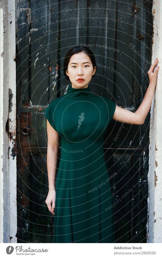 Asiatin, die sich an die Wand lehnt. Frau Jugendliche attraktiv Kleid grün Japaner anlehnen