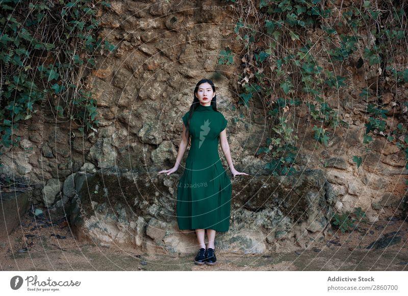 Hübsche asiatische Frau am Teich sitzend Jugendliche attraktiv Kleid rot lügen Bank Holz Blick in die Kamera schön Beautyfotografie Mensch hübsch Dame Porträt
