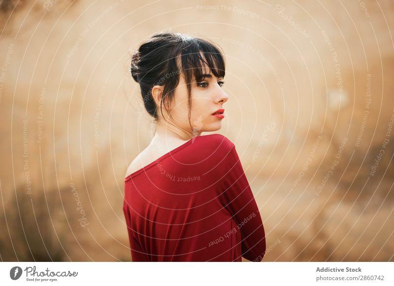 Verführerisches Modell in rotem Kleid Frau verführerisch reizvoll Beautyfotografie Anmut romantisch genießen Haut Figur brünett selbstbewußt Körperhaltung
