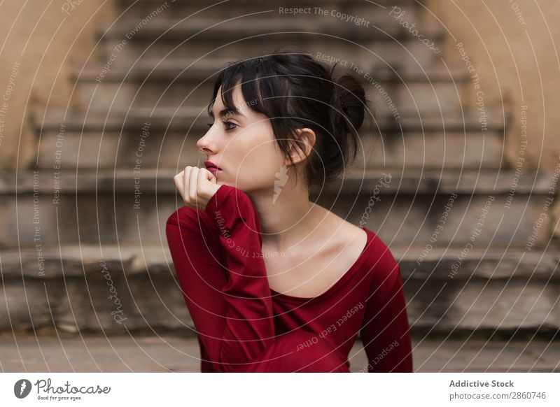 Zartes Mädchen in rot, das wegblickt. Frau bezwingbar Beautyfotografie Auge Blick sitzen Körperhaltung genießen Treppe Mode Anmut Fürsorge Angebot zart