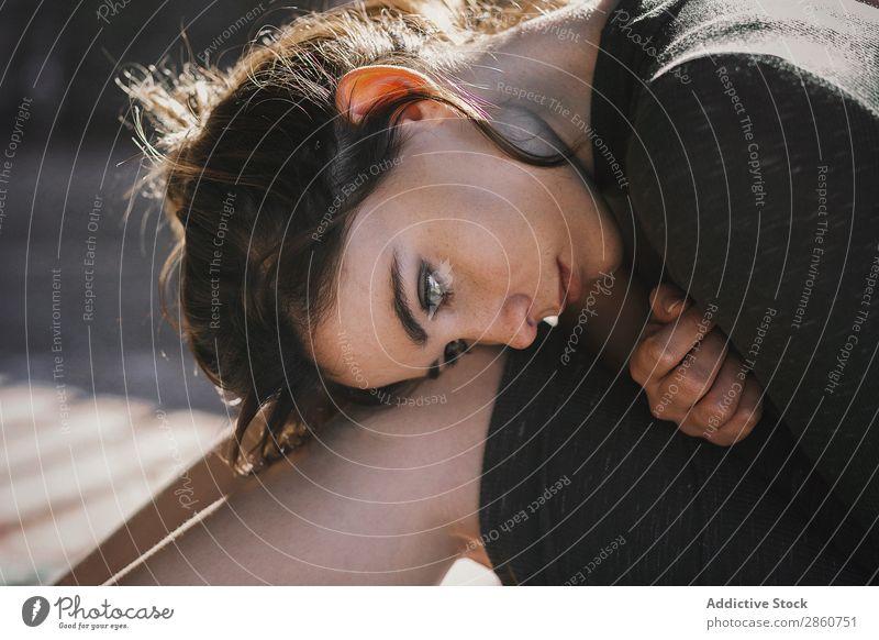 Sinnliches Mädchen sitzt auf dem Boden in der Sonne. Frau Schatten genießen Sonnenlicht Streifen Hochsitz sitzen Etage Körperhaltung Morgen Kleid Barfuß hell