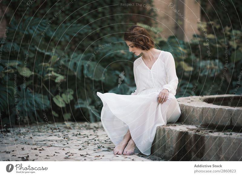 Attraktive Frau am Teich im Park Jugendliche attraktiv Kleid weiß sitzen Beton Wald Blick in die Kamera schön Beautyfotografie Mensch hübsch Dame Porträt Mode