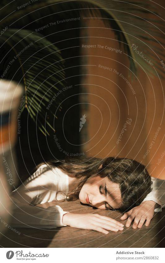 Frau, die sich lehnt und auf dem Tisch schläft. Jugendliche attraktiv Kleid weiß lügen schlafen aussruhen