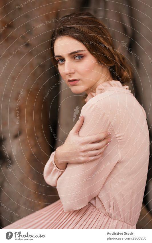 Frau, die auf die Kamera auf dem Baum schaut. hübsch Jugendliche Kleid altehrwürdig retro rosa groß Wurzel Wegsehen schön attraktiv Mensch Beautyfotografie