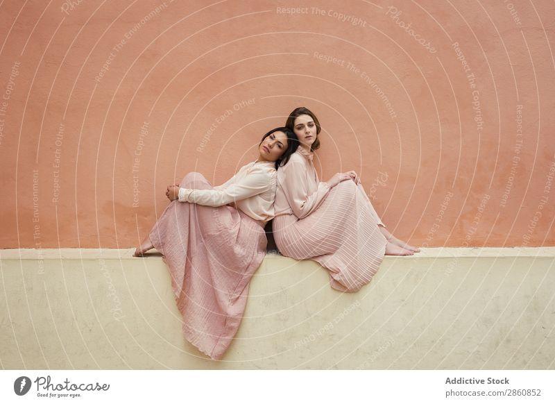 Frauen sitzen zusammen an einer orangefarbenen Wand. hübsch Jugendliche schön anlehnen Rücken an Rücken Fürsorge besinnlich Partnerschaft lgtb Freundschaft