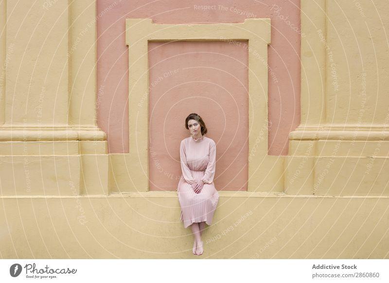 Frau in rosa Kleid, die an der Wand posiert. hübsch Jugendliche altehrwürdig Körperhaltung sitzen schön attraktiv Mensch Beautyfotografie Erwachsene Stil