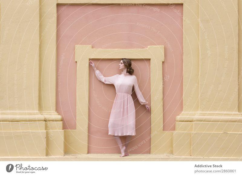 Frau in rosa Kleid, die an der Wand posiert. hübsch Jugendliche altehrwürdig Körperhaltung stehen sitzen schön attraktiv Mensch Beautyfotografie Erwachsene Stil