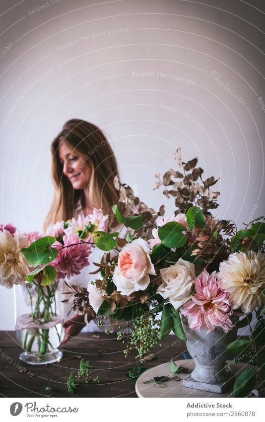 Frau am Tisch mit Blumensträußen in Vasen Blumenstrauß Pflanze Chrysantheme Rose Zweig Glück frisch Haufen Blatt Holz Dame Ast Blütenknospen Natur Kreativität