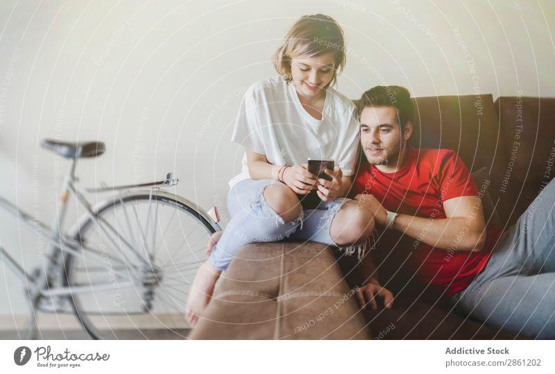 Koppelung auf dem Sofa auf dem Handy Paar heimwärts Zusammensein Glück sprechen interagierend Lächeln Kaffee Liebe Mensch Lifestyle Jugendliche lässig