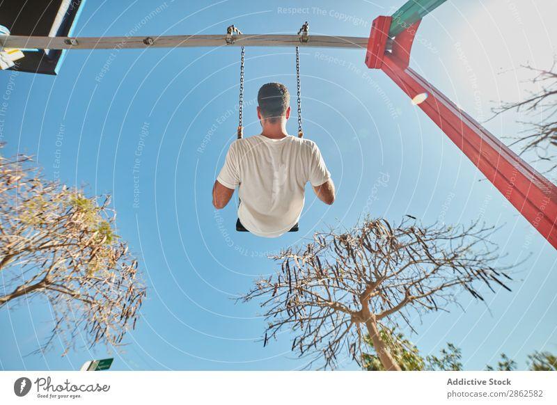 Mann schwingt auf dem Spielplatz bei Sonnenlicht Schaukeln Freizeit & Hobby Stadt hell Blauer Himmel Zufriedenheit Straße Aktion Ausdruck Spielen