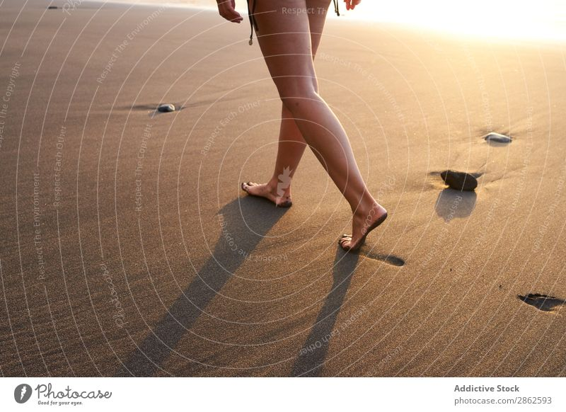 Getreidefrau, die auf dem Sand des Strandes spazieren geht. Frau Fußspur laufen Freitreppe Sonnenlicht abgelegen Sommer Meer sanft Küste Fußtritt