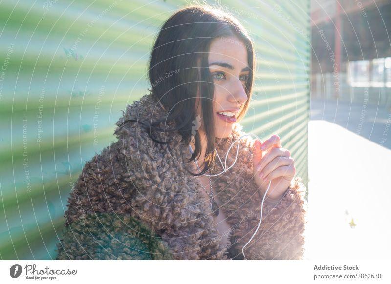 Trendige Frau mit Smartphone an der Wand PDA benutzend Straße Großstadt anlehnen Stil Jugendliche Sonnenstrahlen Tag genießen trendy Mode Outfit Außenseite