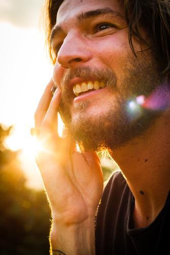 Sunny Call Mann Mensch Jugendliche Junger Mann Bart alternativ Rocker Vollbart Telefon Telefongespräch Handy lachen Lächeln Freude lustig spaßig Gegenlicht