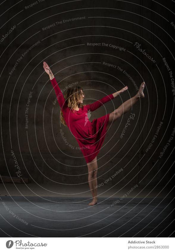 Junge Frau mit hochgezogenem Bein in der Dunkelheit Balletttänzer Ballerina Tanzen Kleid Beine Hand erhöht Leistung Raum rot elegant dunkel Kunst Pose Show