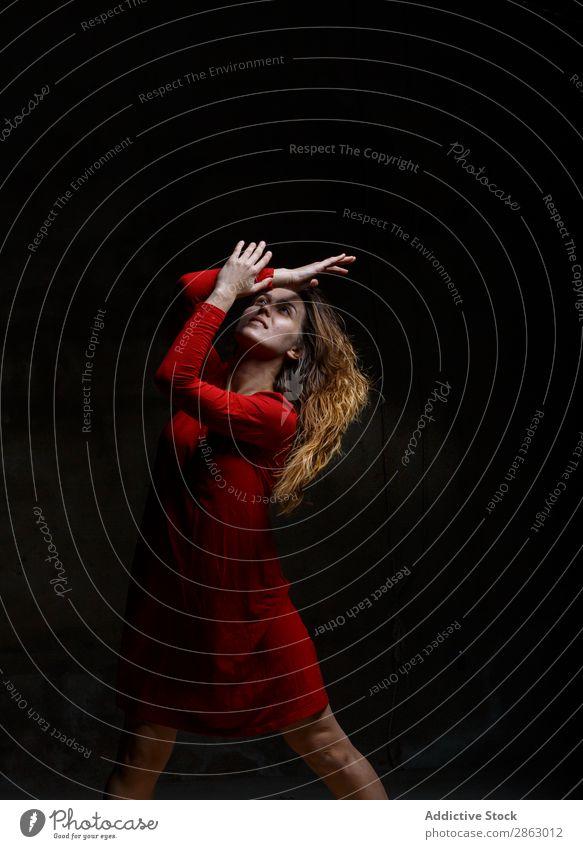 Junge Frau tanzt in der Dunkelheit Balletttänzer Tanzen Ballerina rotes Kleid Hand Leistung Raum elegant dunkel Kunst Pose Show Kittel Obskurität Anmut Turnen