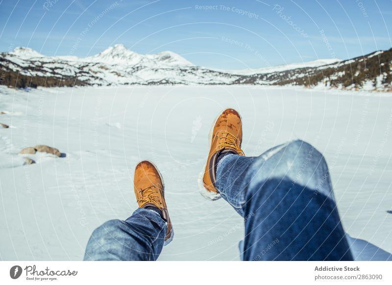 Männerbeine in Winterstiefeln auf Schnee in der Nähe von Bergen Mann Stiefel Berge u. Gebirge cerdanya Frankreich Beine Jeanshose Schönes Wetter Hügel sitzen