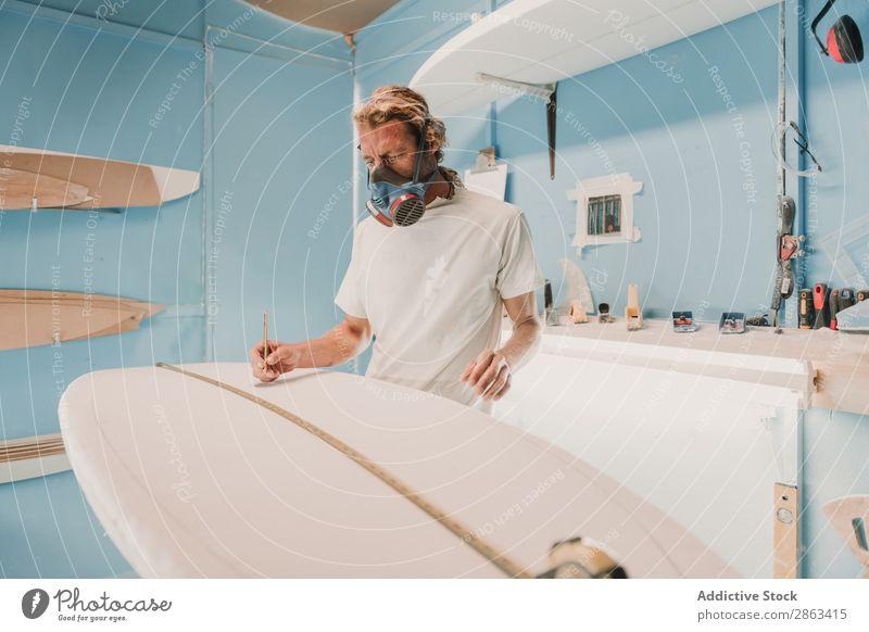 Mann in Atemschutzgerät misst Surfbrett in der Werkstatt Messung Schreinerei Arbeitsplatz Bleistift Verschnaufpause Werkzeug Zimmerer Waffe Holz Konstruktion