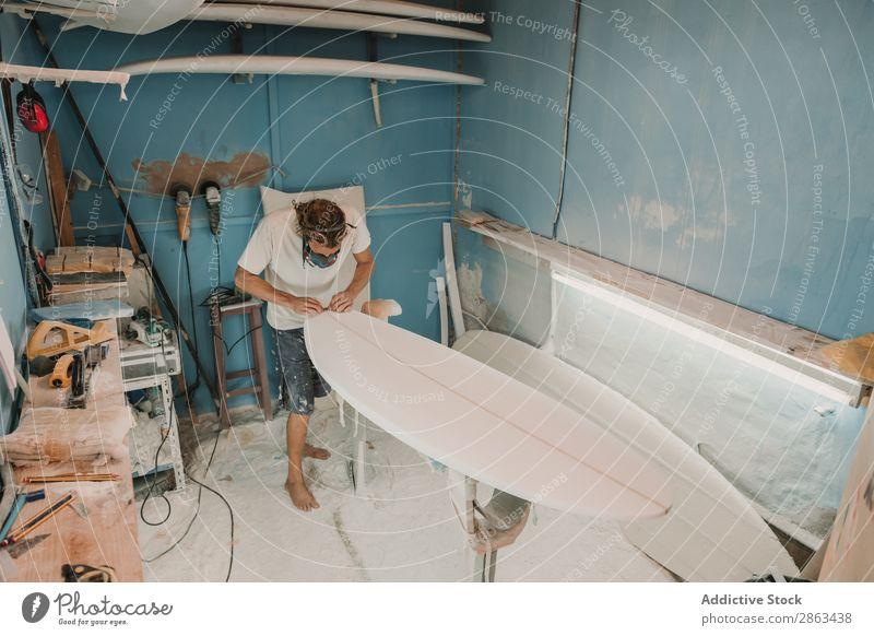 Mann in Atemschutzgerät poliert Surfbrett in der Werkstatt Polieren Schreinerei Schleifpapier Arbeitsplatz Verschnaufpause Zimmerer Werkzeug Waffe Holz