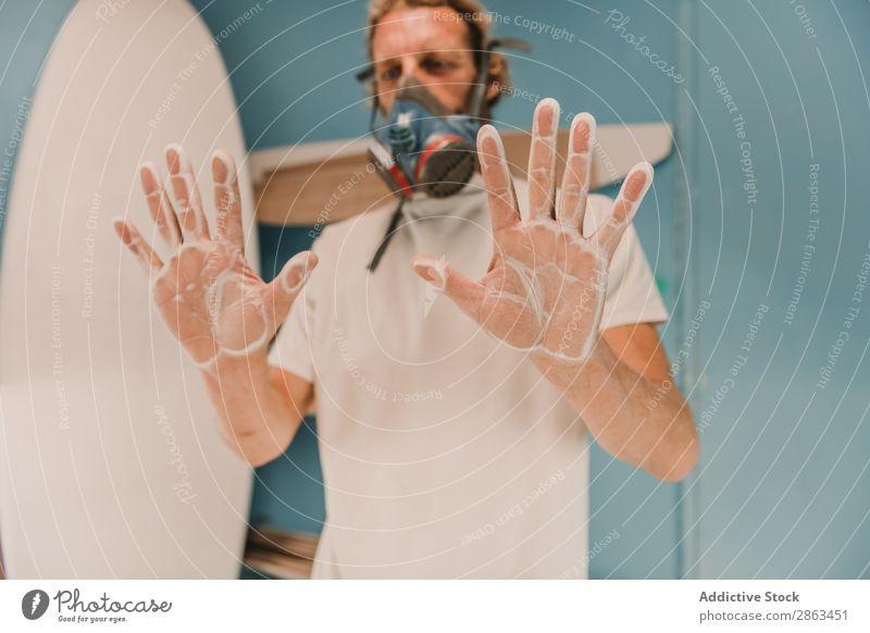 Mann in Atemschutzmaske mit Händen im Staub Atemschutzgerät Hand Werkstatt Surfbrett zeigen Holz Handfläche Schreinerei Arbeitsplatz Verschnaufpause Zimmerer