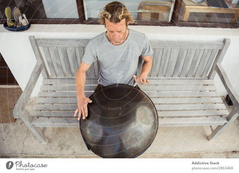 Blonder Mann auf der Bank sitzend mit großer Handtrommel Trommel Handkurbel Barfuß T-Shirt Sitz blond Fenster Tür Gebäude Musik Typ Instrument Spielen Klang