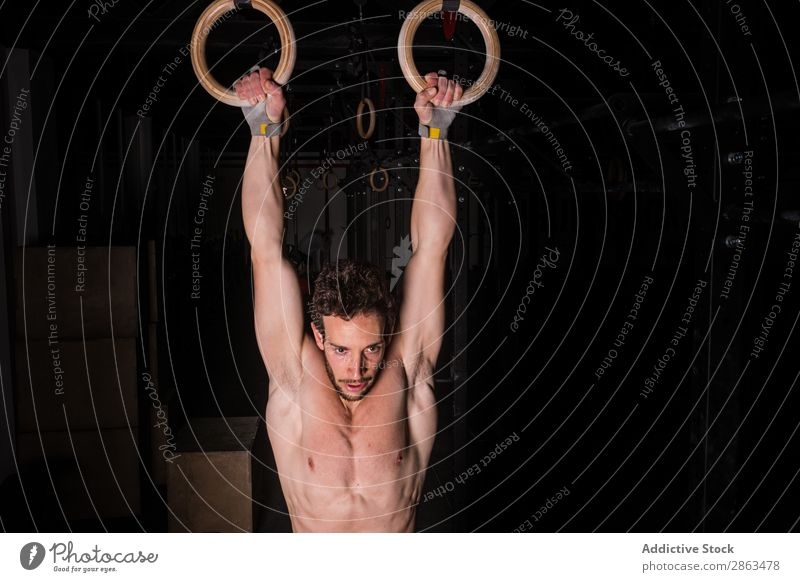 Mann hängt an Gymnastikringen zwischen Dunkelheit im Fitnessstudio. gymnastisch Ring Sporthalle erhängen sportlich Jugendliche ohne Hemd Obskurität Typ Gerät