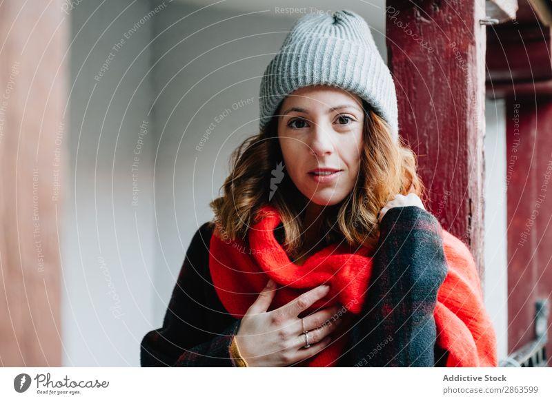 Positive Frau in warmer Kleidung in der Nähe des Hauses Freundlichkeit Wärme Hand Brust anhaben positiv Winter Jugendliche Gebäude Dame Lifestyle rothaarig
