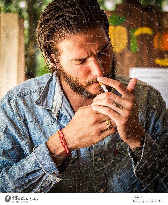 smokie Mann Mensch Junger Mann Zigarette anzünden Rauchen Tabakwaren Feuerzeug schön Jugendliche Tattoo tätowiert Bart Vollbart sitzen Café Außenaufnahme Hand