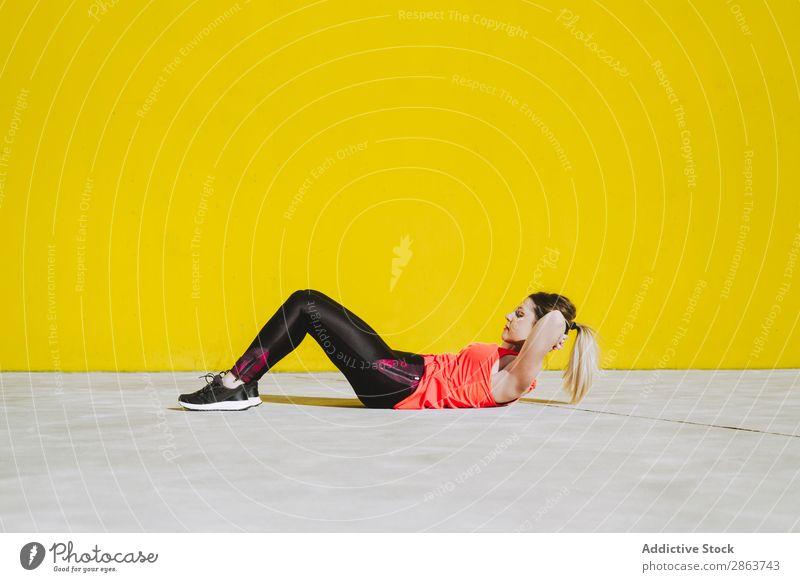 Frau, die Sitzübungen auf dem Boden macht. Sit-ups üben Sportbekleidung sportlich Jugendliche Etage Fitness Training Wand Presse gelb Dame Gerät Kraft dünn