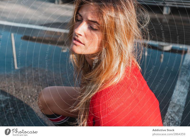 Charmante Frau im Pullover auf der Straße zwischen den Pfützen. blond charmant Dame genießen Kniestrumpf Slop Jugendliche Model rot Wasser Entwurf sitzen