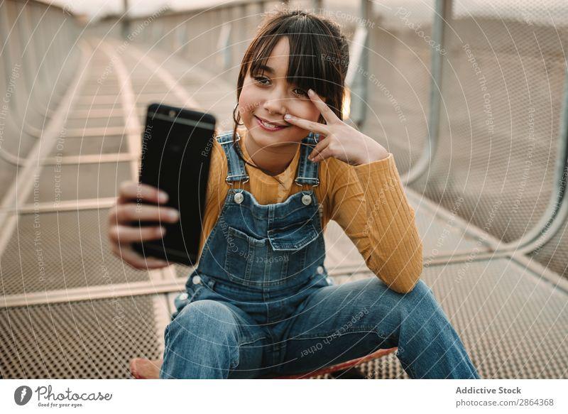 Lustiges Mädchen nimmt Selfie auf dem Smartphone auf dem Laufsteg. Jugendliche PDA Gang Fußweg lustig Großstadt Stil